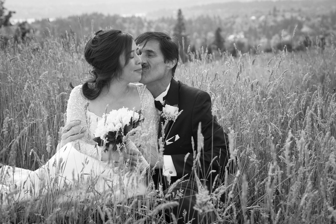 Bride and groom sitting and kissing in the tall grass at Newcastle Golf Club