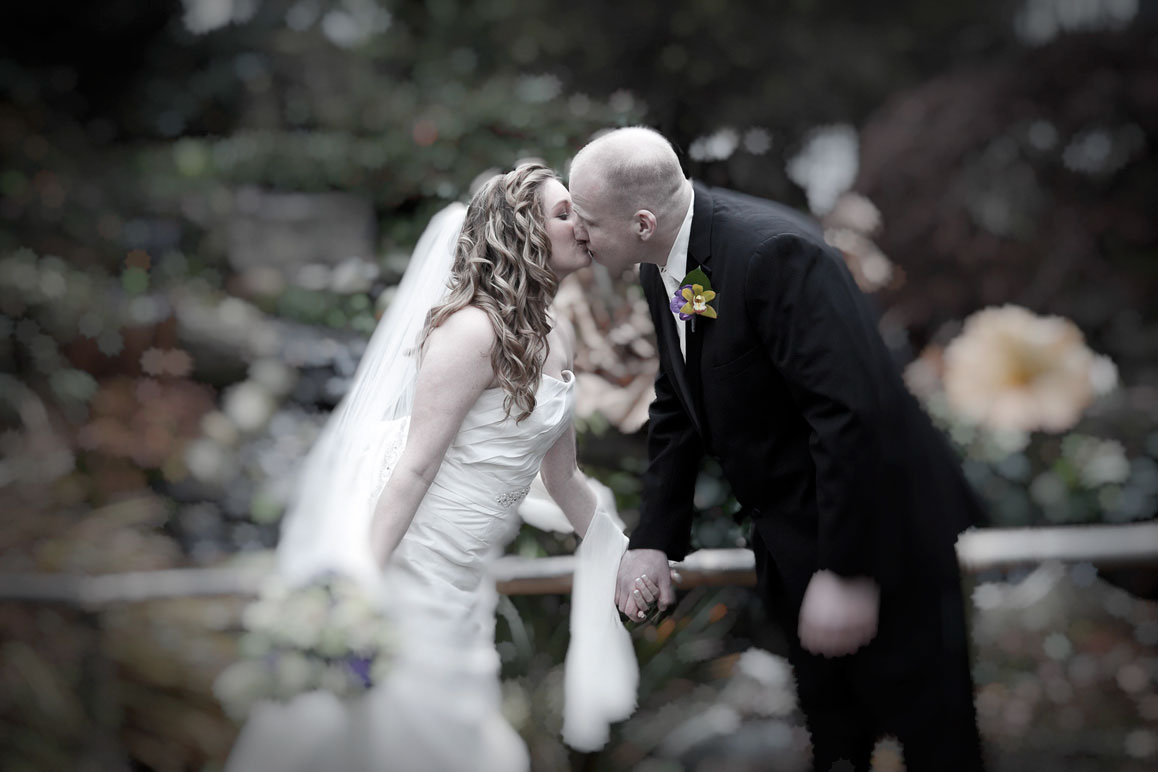 Soft-focus photo of bride and groom kissing at Windmill Gardens