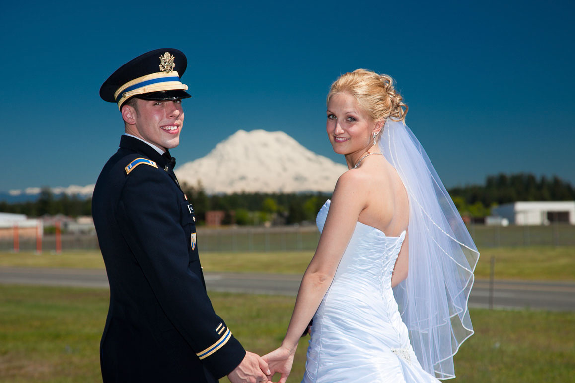 Bride with groom in military dress uniform at Fort Lewis, Mt Rainier in the baqckground
