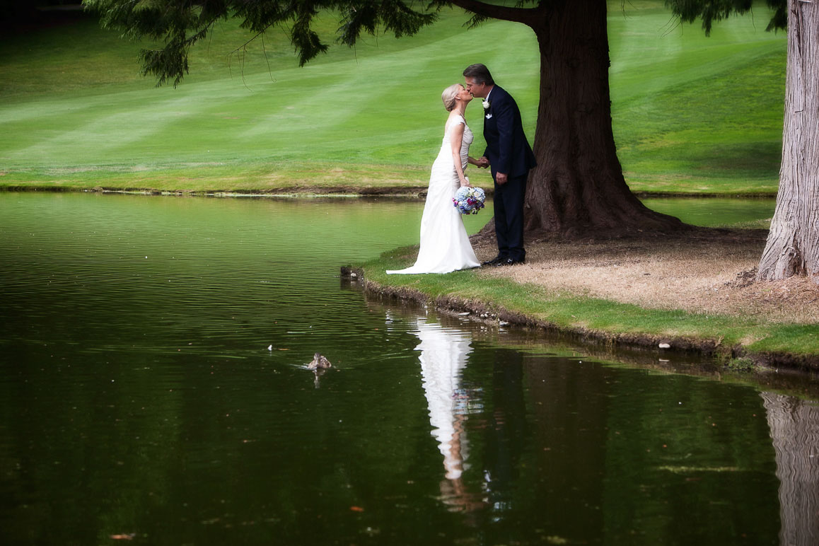 Bride and groom share a kiss while standing along a beautiful pond, with reflection in the water