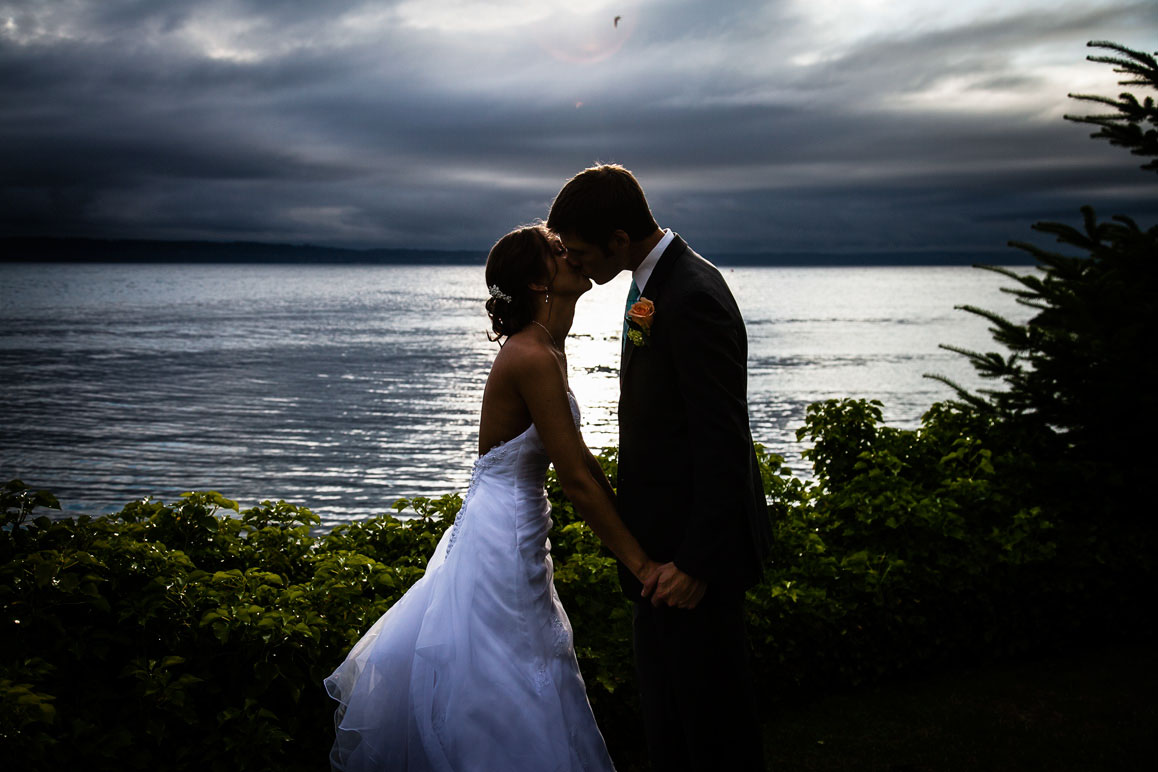 Backlit sunset photo of bride and groom kissing at Shilshole Bay Beach Club