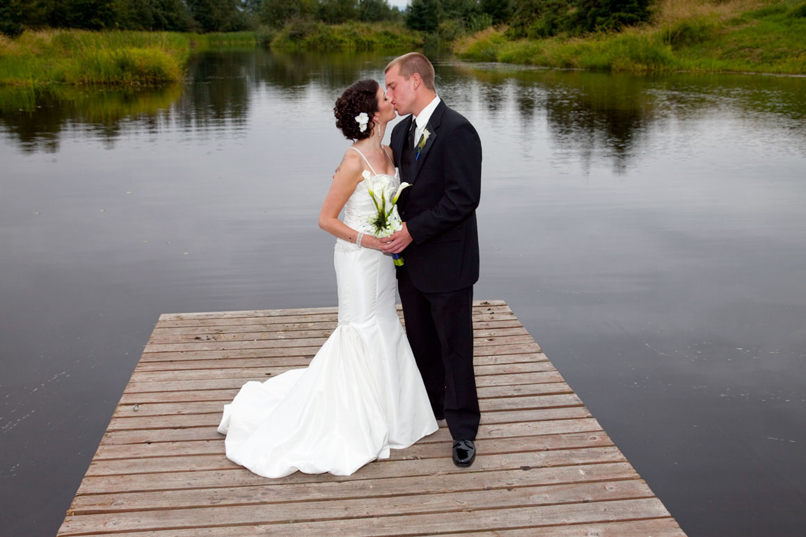 Bride and groom standing on dock and kissing at Lord Hill Farm in Monroe