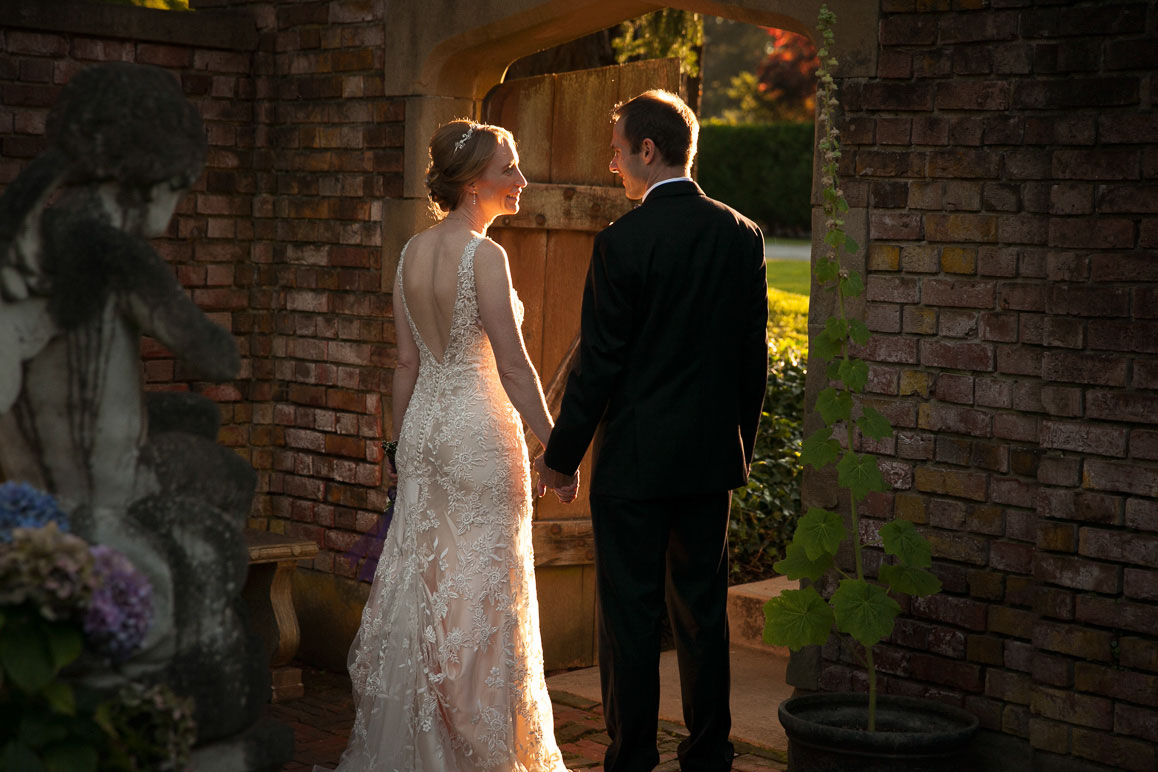Backlit bride and groom holding hands while standing in rock archway