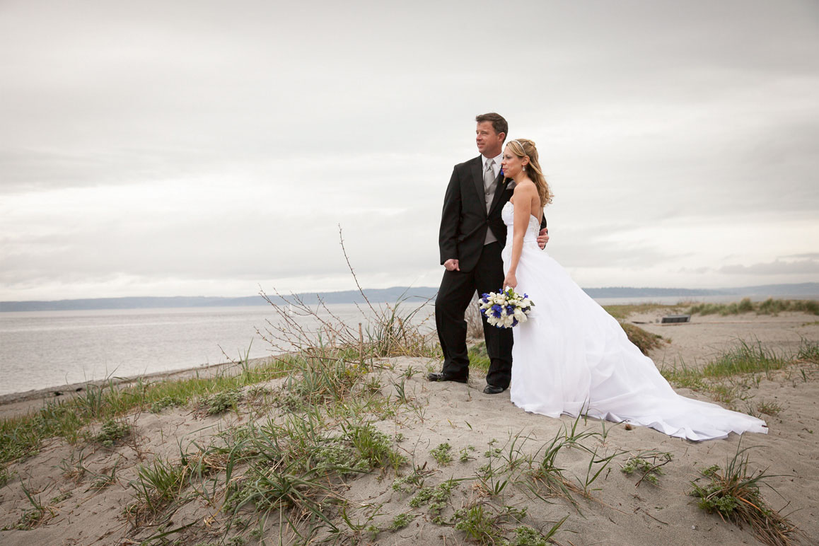 Wedding photo of couple standing on the sand dunes at Golden Garden Park in Seattle