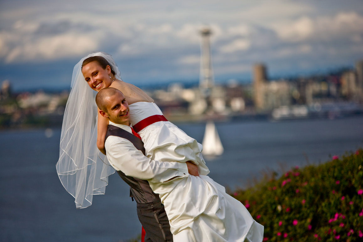 Groom carrying bride with Seattle and Space Needle in background in West Seattle