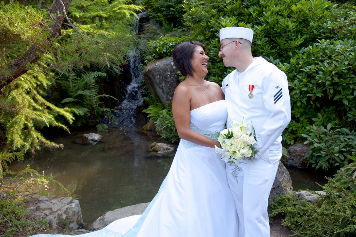 Bride with groom in Navy uniform hugging next to waterfall at Kubota Gardens