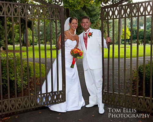 Bride and groom standing at the gates of Clise Mansion, at Marymoor park in Redmond